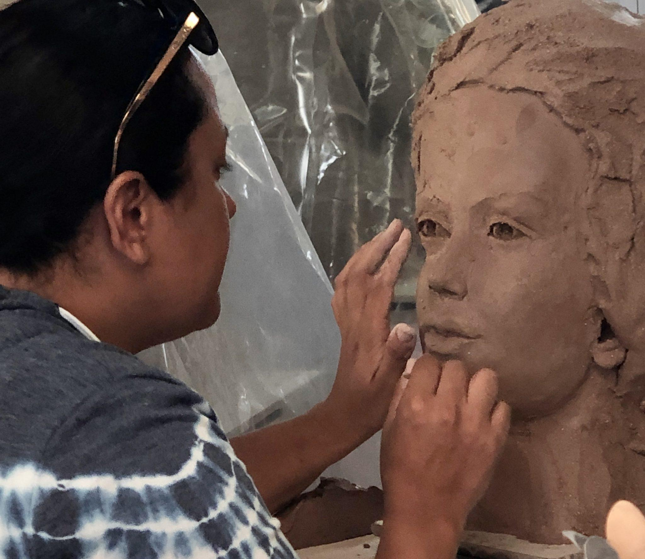 Esperanza working on the eyes of her clay sculpture
